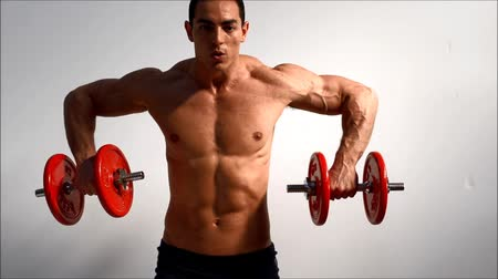 levantamento de pesos : Young handsome male bodybuilder training shoulders with dumbbells, against light background Vídeos