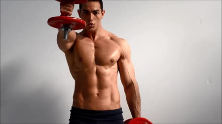 male : Young handsome male bodybuilder training shoulders with dumbbells, against light background Stock Footage