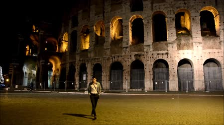 roma : Stylish handsome young man walking in front of Colosseum in Rome, Italy, alone at night Stok Video