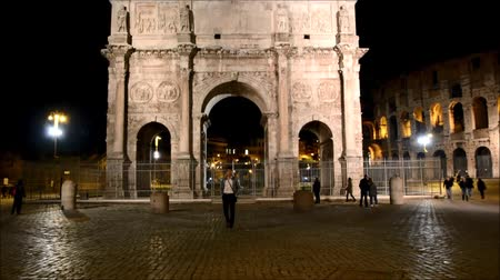 costantino : Stylish handsome young man walking in front of Arco di Costantino in Rome, Italy, alone at night