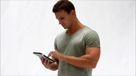 мышечный : Muscular young man standing while reading from e-book device or using tablet PC, on white background