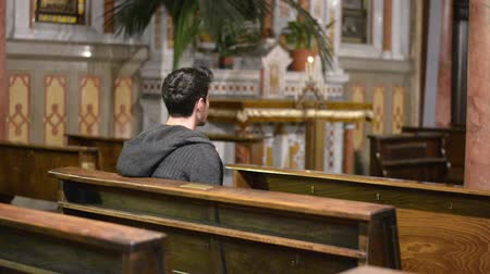 dua eden : Young man praying in church Stok Video