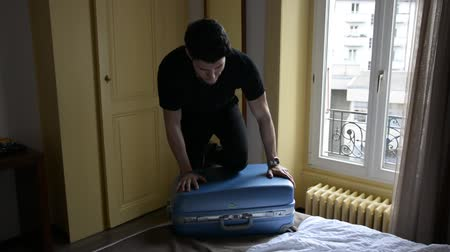 feszült : Young man trying to close his suitcase Stock mozgókép
