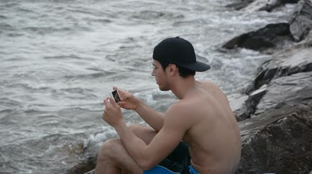 pic : Shirtless Young Handsome Man Busy with his Mobile Phone Taking Selfie Photo While Sitting on Beach Boulders next to Sea or Ocean Stock Footage