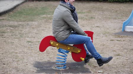 delirar : Young man reliving his childhood plying in a childrens playground riding on a colorful red spring seat with a happy smile in an urban park.