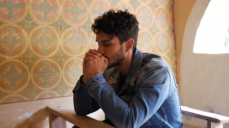 dua eden : Young man sitting and kneeling in small chapel praying Stok Video