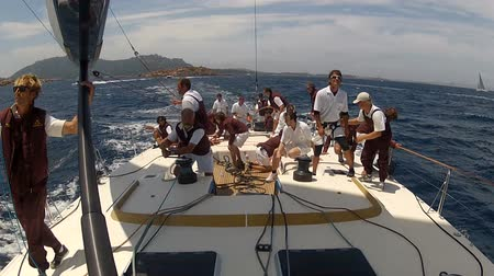 гонка : Crew of sailing boat maneuvering during regatta. Action cam on board attached to the mast