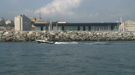 area of port : Boat navigating in front of the Genoa Boat Show exhibition area