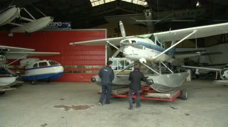 hydroplane : Men moving float plane outside hangar full of planes