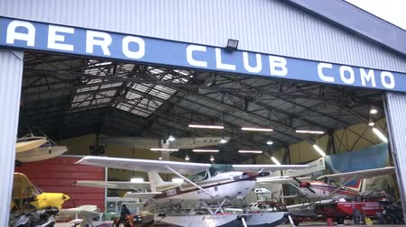 hydroplane : Hangar full of float planes in Como, Italy, with small tractor moving a plane