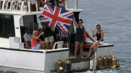 regaty : People on a boat attend Americas Cup World Series in Hamilton, Bermuda, waving a Great Britain flag