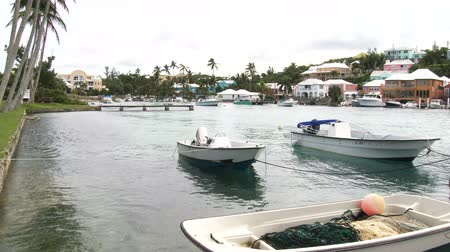 Kleine boten aangemeerd in een baai in Flatts Village, Bermuda Stockvideo
