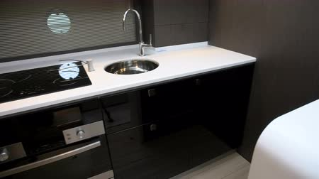 Fancy white kitchen with induction hob on the lower deck of a boat Wideo