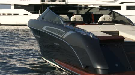 mükemmellik : Luxury Riva boat anchored in a bay, beside the maxi yacht, during the Cannes yachting festival Stok Video