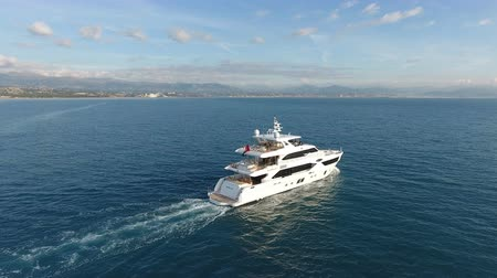 Aerial view of 110 feet long luxury yachts navigating slowly on the calm sea, close to the French coast