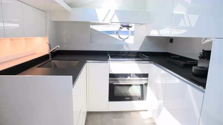 Bright white kitchen with black counter on a super yacht Wideo