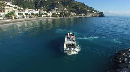 Aerial view of a ferry transporting passengers maneuvering at the entrance of a small port near Amalfi, Italy
