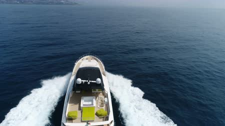 mükemmellik : Aerial view of a luxury yacht navigating fast at the open sea, with drone passing on top of it.