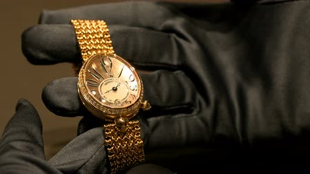 booth : Detail of hands of an horologist holding a luxury watch at Breguet booth at Baselworlds watches and jewelry show in Basel, Switzerland. Stock Footage