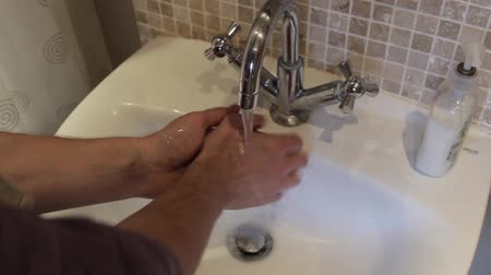 lavatório : Man turns on tap and washes hands in sink