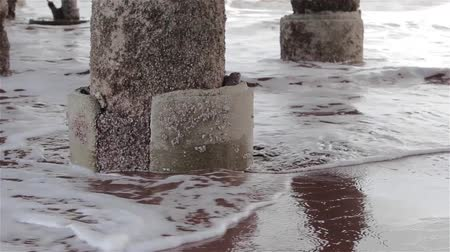 atracação : Gentle Sea Waves Wash Concrete Pillars at Base of Pier on Teignmouth Sand Beach Stock Footage