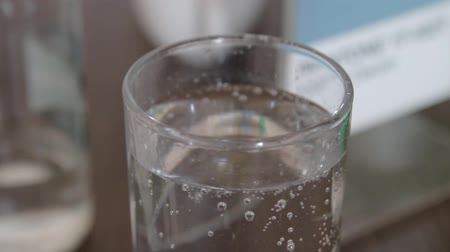 fizzing : Many Bubbles burst on the surface of a glass of water