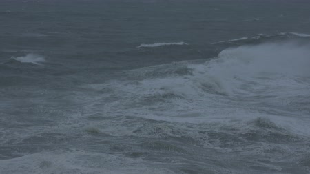 handheld shot : Slow-motion handheld footage of waves on the Oregon coast filmed in the evening during wind and rain.