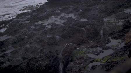 Slow-Motion footage of water dripping off the rock wall at Depoe Bay, OR taken on a stormy day.
