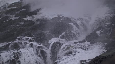 Slow-motion footage of water shooting up through the rocks and then flowing back down in Depoe Bay, OR on a stormy day.