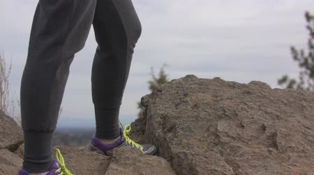 Footage of a woman at the end of a hike standing on a rock.