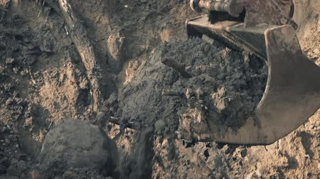 clearing away : Closeup of large mechanical digger arm scooping up soil and debris and depositing it in a pile Stock Footage