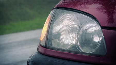 Front light on car flashing as cars pass nearby in rainy weather Stok Video