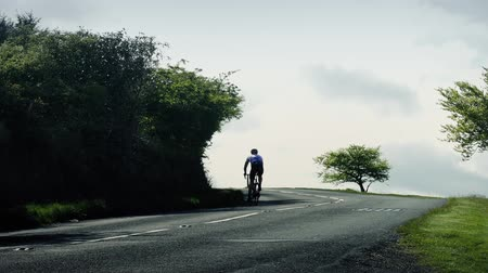 cyclists : Cyclist Rides Up Hill At Sunset With Car Passing Man cycles on road in the country with a car passing Stock Footage
