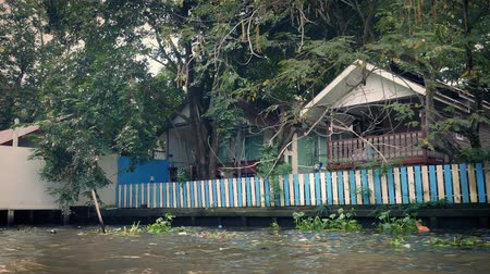 tin roofs : Boat POV Passing Riverside Houses In Thailand Stock Footage