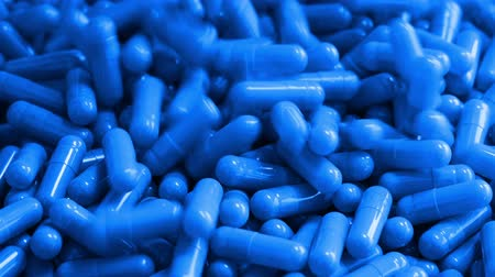 Blauwe farmaceutische capsules gieten in stapel close-up