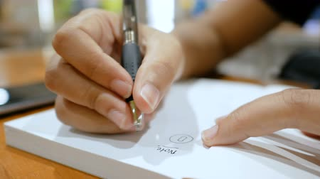 imzalama : Close up shot hands of woman writing on paper notebook select focus shallow depth of field Stok Video