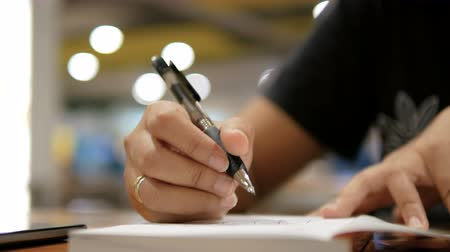 table top shot : Close up shot hands of woman writing on paper notebook select focus shallow depth of field Stock Footage