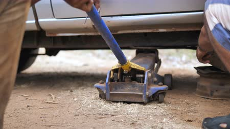 Hands of mechanic using car jack to lift up the truck to repair wishbone control arm and replace the front wheel of the car