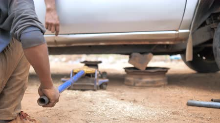 гидравлический : Hands of mechanic using car jack to lift up the truck to repair wishbone control arm and replace the front wheel of the car