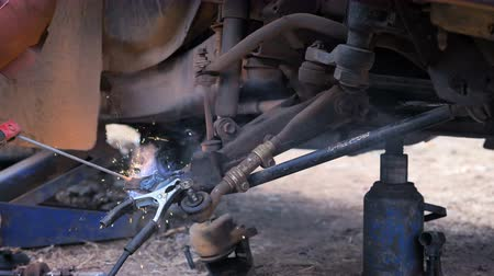 Hands of mechanic welding for repair the truck wishbone control arm of front wheel with dark and grain processed
