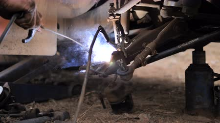 処理された : Hands of mechanic welding for repair the truck wishbone control arm of front wheel with dark and grain processed