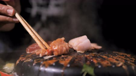 dark roast : People using chopstick to cooking pick up and flip pork and meet of Korean BBQ barbecue on the hot pot with dark and grain processed