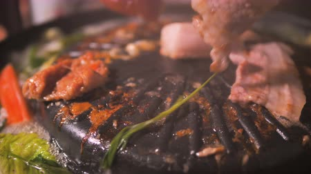 People using chopstick to cooking pick up and flip pork and meet of Korean BBQ barbecue on the hot pot with dark and grain processed