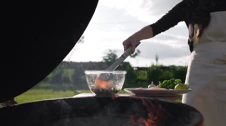kalmar : The cook puts raw calamari to the self cooked sauce before roasting on the open fire on grill, making barbecue with seafood products, grilled squid, cooking outdoors