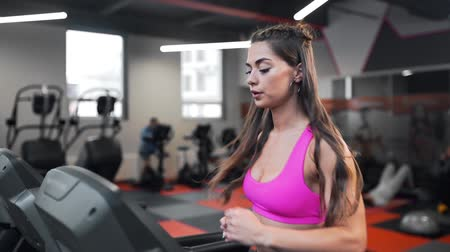 Beautiful attractive woman with curly long hair in pink sportswear runs on the running track, fitness on the treadmill, woman maintains an excellent shape in the gym, fit body, perfect body shape