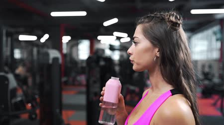 Beautiful attractive woman drinks water from bottle at the gym after hard working on the simulators, woman rests after workout, sport and workout Stok Video