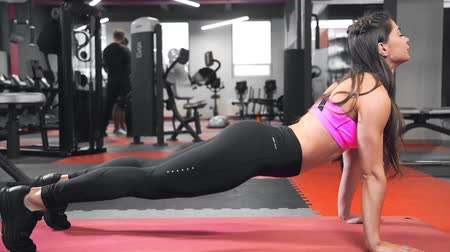 Beautiful sexy woman in tight fitting sportswear stretches after training at the gym, perfect body and shape, fitness and workout, hot body