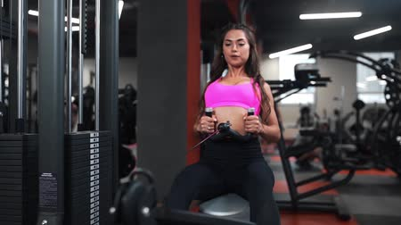 Beautiful woman at the sports club does different kind of exercises on the simulators for being in good shape, fitness and beauty, cardio and strength exercises, sporting club