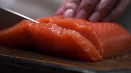potraviny : The cook cuts salmon fillet, chef prepares fish for cooking, dishes with fish, diet food