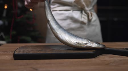 Chef puts herring fish to the wooden board and prepares for cooking, making of fish meals, dishes with fish, food cooking in the kitchen Stok Video